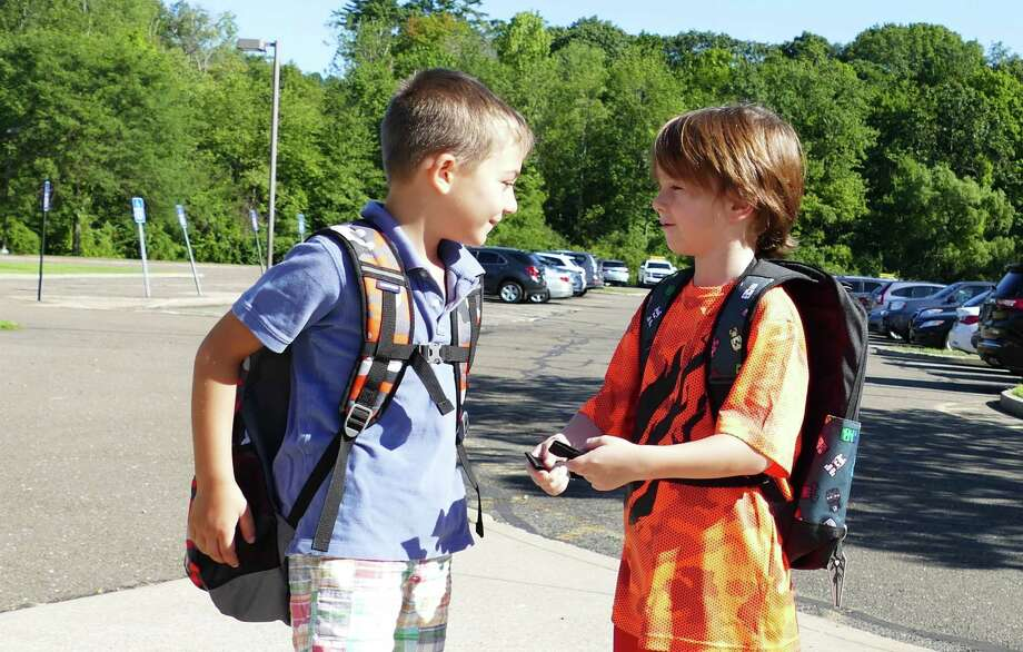 T.J. Hahn, 6, greeted his pal Max Frattaroli, 5, in front of East School in New Canaan on a recent first day of school in the town. Moments before they had hugged each other hello. Sharing will be discouraged when the town's public schools re-open in the fall amid the coronavirus pandemic. Photo: Grace Duffield / Hearst Connecticut Media