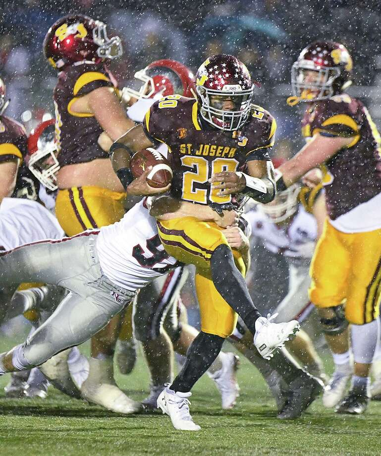 St. Joseph's Jaden Shirden runs for more yardage in the rain against New Canaan in the Dec. 9 CIAC Class L semifinal game. Shirden accounted for 257 yards and five scores to help St. Joseph to victory. Photo: David G Whitham / For Hearst Connecticut Media / DGWPhotography