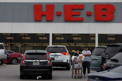 Shoppers with a full cart leave the HEB in the Brook Hollow Shopping Center in San Antonio, Texas, on March 13, 2020.