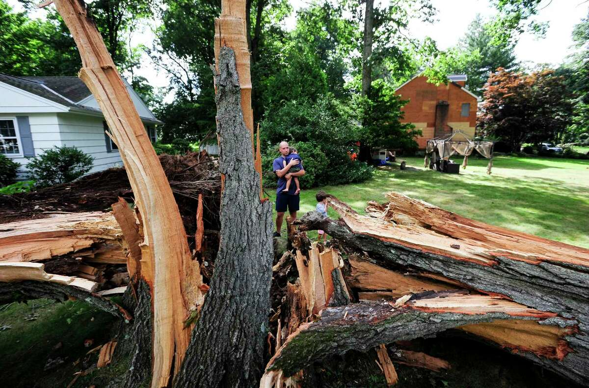 Tyler Maloney holds his 1-year-old son Bear while being photograph near a large tree that fell during the storm in front of his home in Stamford on Aug. 8. The tree cut power and access to his neighborhood.