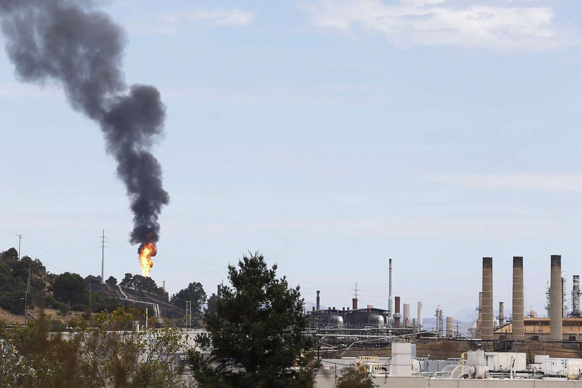 smoke and flames shoot yo from a building near the Chevron oil refinery in Richmond, Calif. Friday, August 24, 2020.