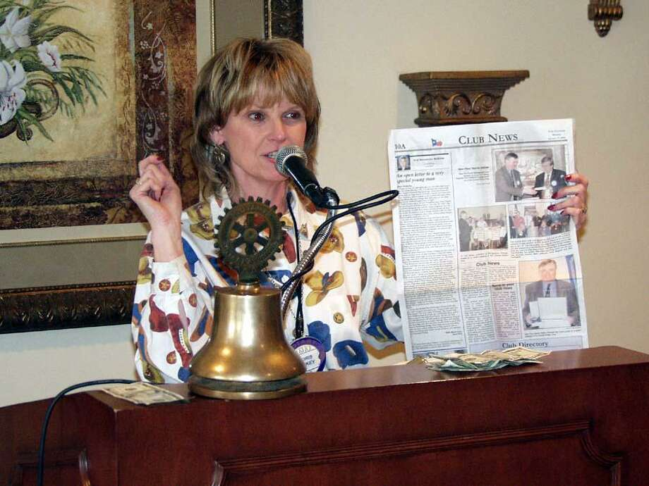 Doris Lockey, Past President of The Rotary Club of Conroe, holds an early edition of the Rotary column, A Rotary Moment, during a Conroe Rotary Club meeting. The column celebrates its 18th anniversary this week. Photo: Courtesy Photo