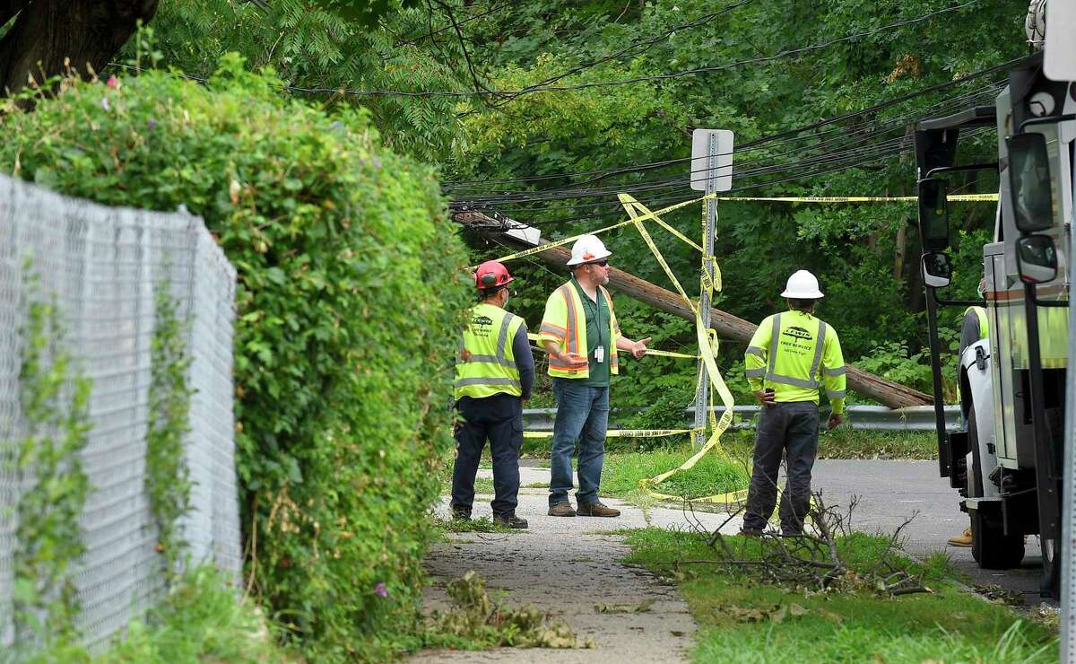 Utility crew stands by as power to the lines is cut by a lineman on Taylor Street in Stamford. Crews from out of state have teamed up with Eversource crews to fix broken poles and clear fallen trees from lines, in an effort to restore power to the region in the wake of damage caused by Tropical Storm Isaias .