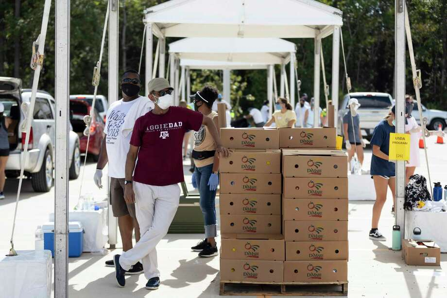 Furthest left, Charles Hayes and Mohammad Tayyab wait for vehicles to pull up during a food distribution event at Planet Ford Stadium in Spring, Tuesday, August 11, 2020. Northwest Assistance Ministries partnered with the Houston Food Bank and Spring ISD to host a Neighborhood Super Site Food Giveaway to assist families facing food insecurity. Photo: Gustavo Huerta, Houston Chronicle / Staff Photographer / Houston Chronicle © 2020
