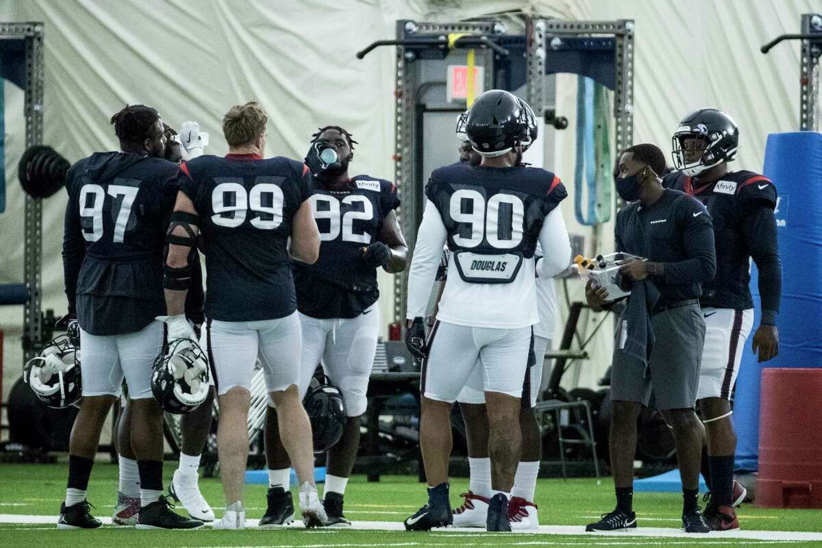 Houston Texans defensive linemen Angelo Blackson (97), J.J. Watt (99), Brandon Dunn (92) and Ross Blacklock (90) take a break between drills during an NFL training camp football practice Friday, Aug. 14, 2020, at The Houston Methodist Training Center in Houston.