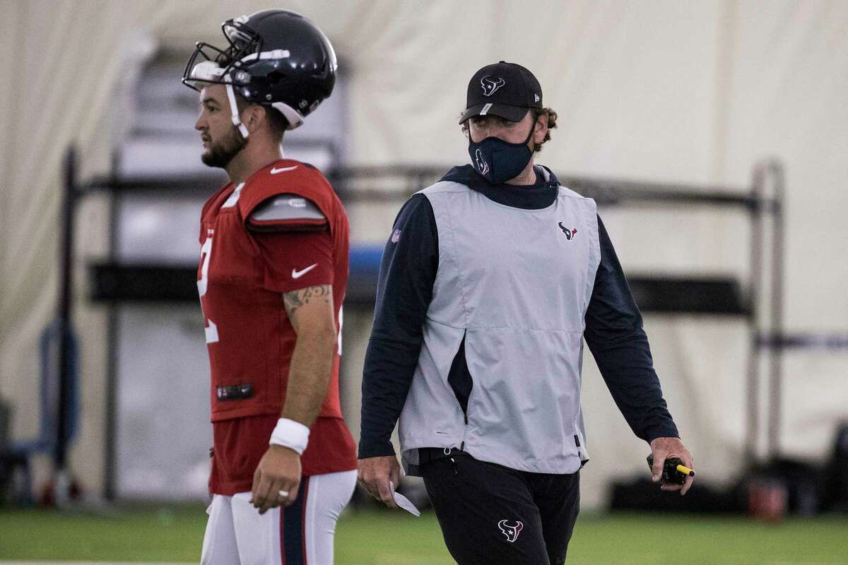 Houston Texans offensive coordinator Tim Kelly works with quarterback AJ McCarron (2) during an NFL training camp football practice Friday, Aug. 14, 2020, at The Houston Methodist Training Center in Houston.