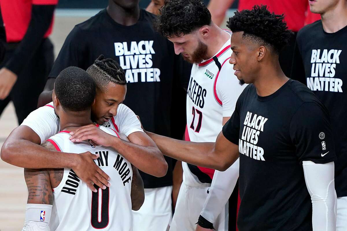 LAKE BUENA VISTA, FLORIDA - AUGUST 13: Damian Lillard #0 of the Portland Trail Blazers is hugged by teammate CJ McCollum #3 after defeating the Brooklyn Nets at AdventHealth Arena at ESPN Wide World Of Sports Complex on August 13, 2020 in Lake Buena Vista, Florida. NOTE TO USER: User expressly acknowledges and agrees that, by downloading and or using this photograph, User is consenting to the terms and conditions of the Getty Images License Agreement. (Photo by Ashley Landis-Pool/Getty Images)