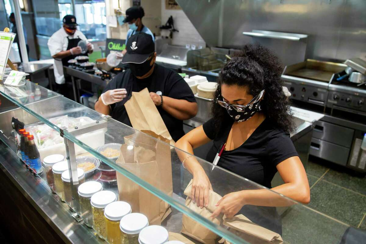 Rene Francis, co-owner of Mediterranean-inspired eatery Oddball Eats, packs dozens of lunch meals for healthcare workers at Finn Hall on Friday, Aug. 7, 2020. Lionstone, which owns Finn Hall, started a drive to support vendors there, encouraging customers to donate $15 meals from Finn Hall restaurants to healthcare workers and matching those donations with its own money.