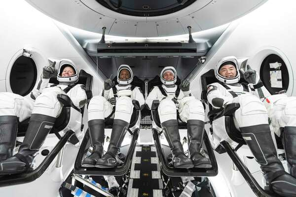 The Crew-1 members are seated in the SpaceX Crew Dragon spacecraft during crew equipment interface training. From left to right are NASA astronauts Shannon Walker, mission specialist; Victor Glover Jr., pilot; and Michael Hopkins, Crew Dragon commander; and Japan Aerospace Exploration Agency astronaut Soichi Noguchi, mission specialist.