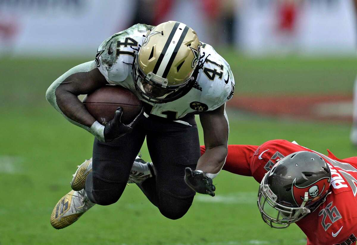 New Orleans Saints running back Alvin Kamara (41) is tripped up by Tampa Bay Buccaneers defensive back Andrew Adams, a former UConn star, during the second half in 2018.