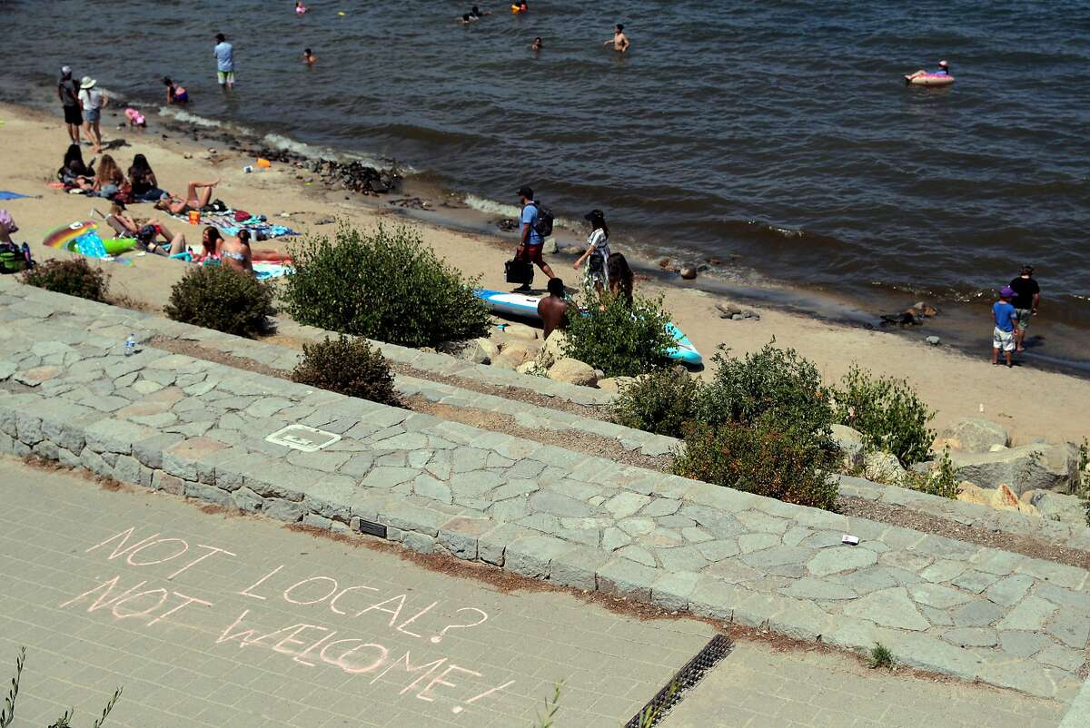 """Visitors play on El Dorado Beach above a promenade where someone had written in chalk, """"Not Local? Not Welcome!"""" in South Lake Tahoe, Calif., on Friday, August 14, 2020. There is tension growing in local communities around the lake as out-of-towners are overrunning the Lake Tahoe beaches, littering and they're not wearing face masks or socially distancing, sparking fears of a coronavirus outbreak in Placer County."""
