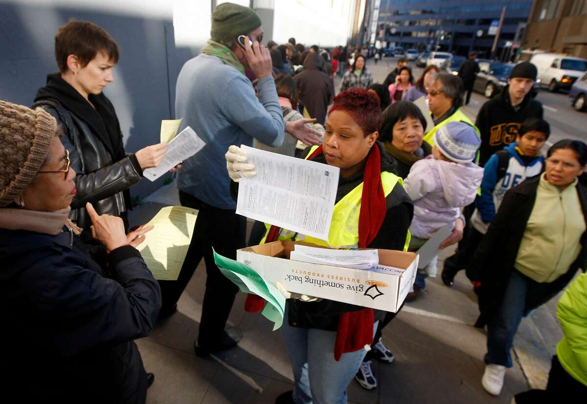 Erica McGary hands out applications to hundreds of people waiting in a line circling the Bill Graham Civic Auditorium for an H1N1 flu vaccination in San Francisco, Calif., on Tuesday, Dec. 22, 2009.