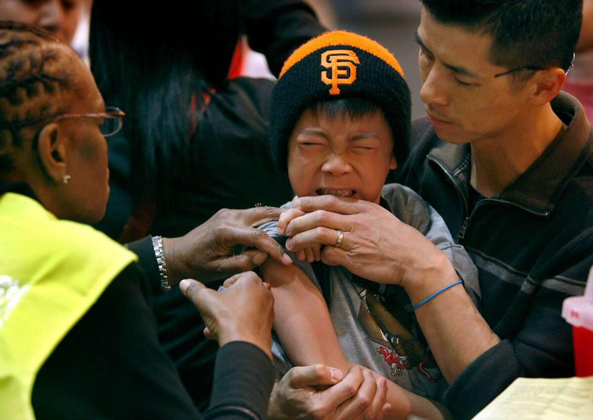 Seven-year-old Ben Ng grits his teeth and is held by his father Eddie Ng as Ivy Steverson (left) vaccinates him against the H1N1 influenza at an all-day innoculation clinic at the Bill Graham Civic Auditorium in San Francisco Tuesday.