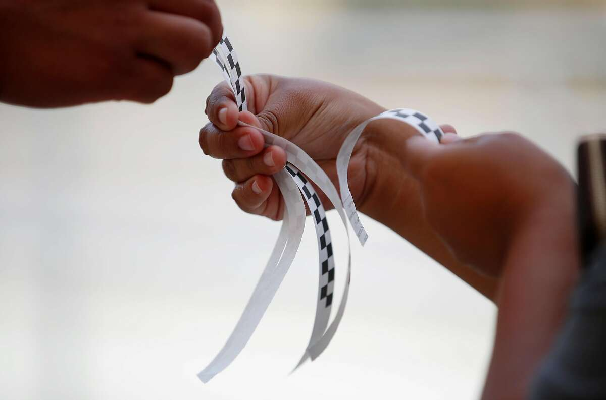 Time slot wristbands are handed out during a Santa Clara County pop-up coronavirus testing event in August. In Gilroy, school officials are urging high school students to get tested following a large party attended by at least one person who later tested positive.