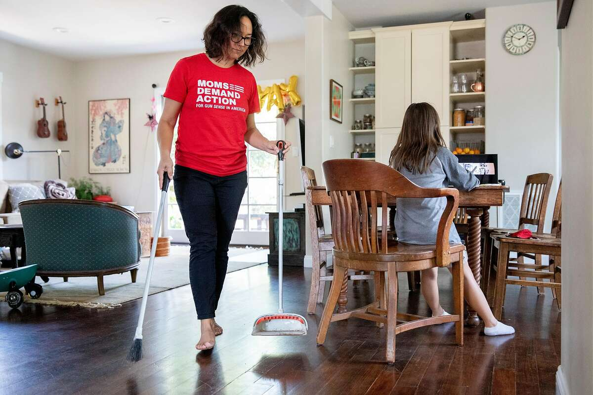 San Mateo City Council Member Amourence Lee sweeps up the kitchen while her daughter Mia Lin, 8, participates in a video chat art class at their home in San Mateo in August.