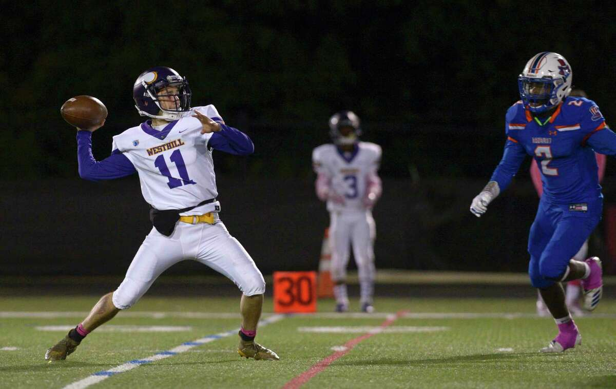 Westhill's Anthony Bivona looks to pass under pressure form Danbury's Malachi Hopkins in an Oct. 4 game.