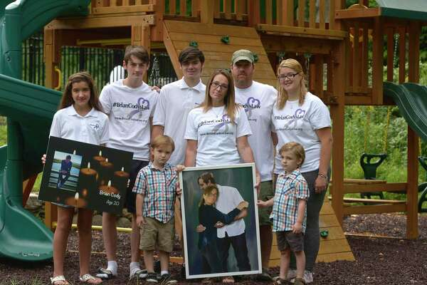 """The family of Brian Cody, Maddy Morrissey, 13, left, Sonny Morrissey, 16, Jayden Cody Morrissey Strongbow Morrissey, 16, Tracey Morrissey, Tony """"Big T"""" Morrissey, Mason Morrissey, 4, and Rachael Morrissey, left, marked the one year anniversary of his fatal overdose this past Monday. New Milford, Conn, Friday, August 14, 2020."""