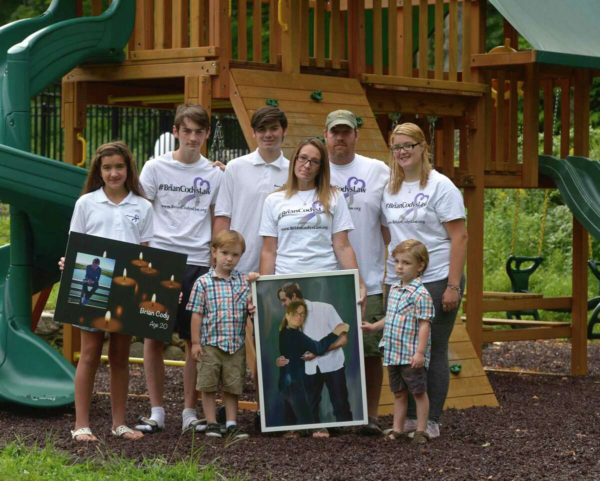 """The family of Brian Cody, Maddy Morrissey, 13, left, Sonny Morrissey, 16, Jayden Cody Morrissey, Strongbow Morrissey, 16, Tracey Morrissey, Tony """"Big T"""" Morrissey, Mason Morrissey, 4, and Rachael Morrissey, left, marked the one year anniversary of his fatal overdose this past Monday. New Milford, Conn, Friday, August 14, 2020."""