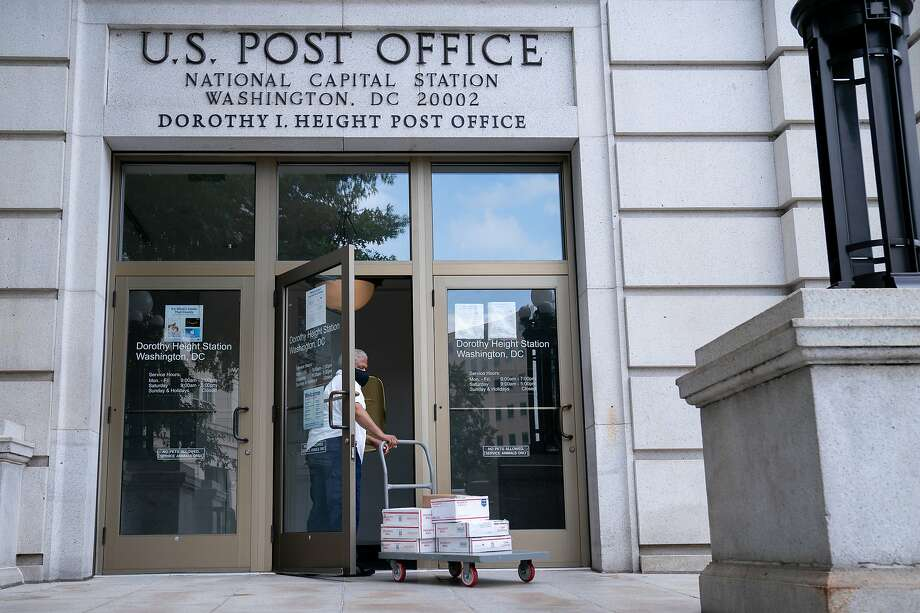 A United States Postal Service (USPS) worker enters a post office near Capitol Hill in Washington, D.C., U.S., on Friday, Aug. 14, 2020. President Trumpyesterday directly tied his opposition to a proposed $25 billion financial lifeline for the Postal Service to his criticism of efforts to encourage mail-in voting during the coronavirus pandemic. Photographer: Erin Scott/Bloomberg Photo: Erin Scott, Bloomberg