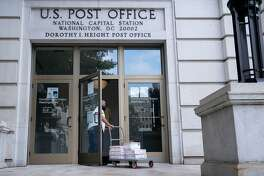 A United States Postal Service (USPS) worker enters a post office near Capitol Hill in Washington, D.C., U.S., on Friday, Aug. 14, 2020. President Trumpyesterday directly tied his opposition to a proposed $25 billion financial lifeline for the Postal Service to his criticism of efforts to encourage mail-in voting during the coronavirus pandemic. Photographer: Erin Scott/Bloomberg