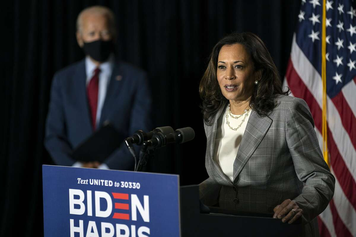 RETRANSMISSION TO REMOVE OUT OF CONTEXT SENTENCE ABOUT SUCCESSION - FILE - In this Thursday, Aug. 13, 2020 file photo, Democratic presidential candidate former Vice President Joe Biden stands at left as his running mate Sen. Kamala Harris, D-Calif., speaks at the Hotel DuPont in Wilmington, Del. On Friday, Aug. 14, 2020, The Associated Press reported on stories circulating online incorrectly asserting Harris is not eligible to serve as president because her parents were immigrants. Harris, 55, was born on Oct. 20, 1964, in Oakland, Calif., making her a natural-born U.S. citizen. (AP Photo/Carolyn Kaster)