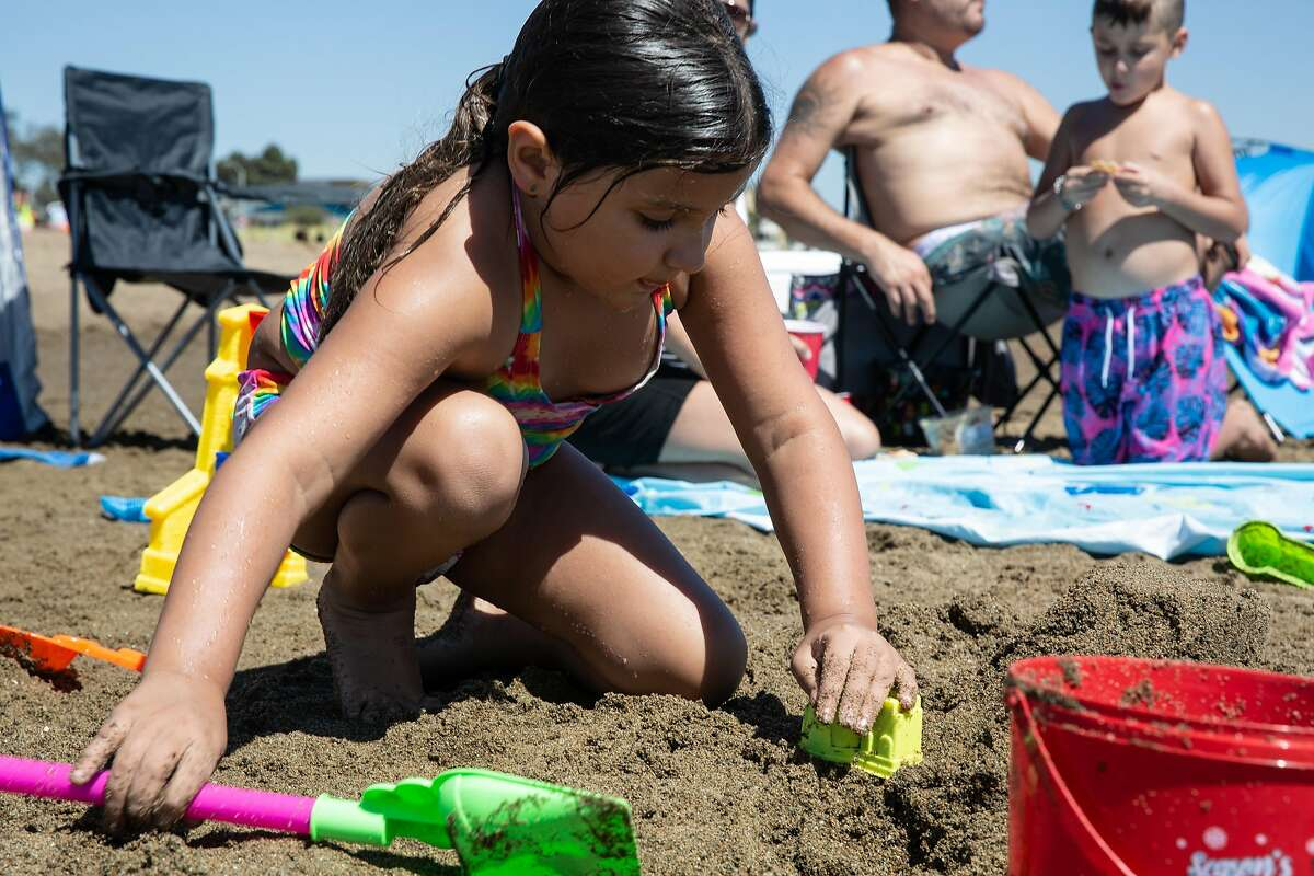 The Ott family soaking up the heat between swims heat at Alameda Beach. Clover Ott (8) builds a sand castle shortly after jumping into the water to freshen up. Alameda Calif. on Friday, August 14th, 2020.