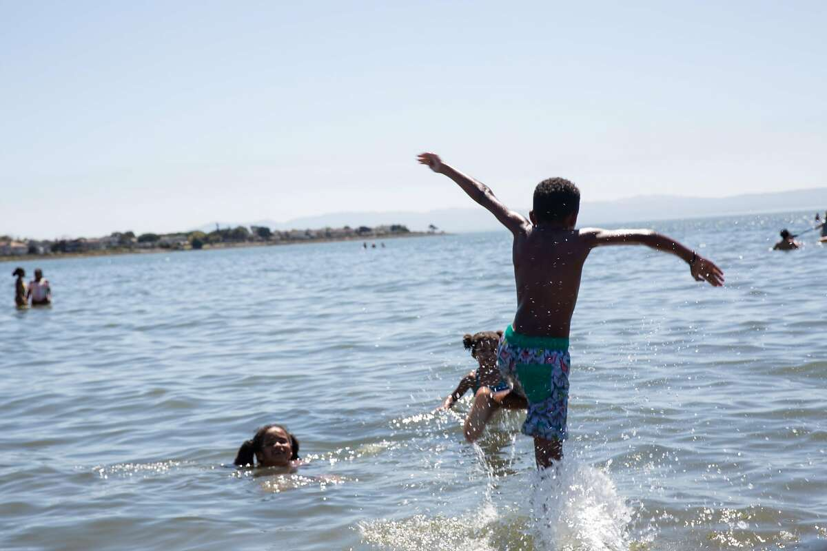 Kaden Jones (8) sprints into the water to play with his siblings Kailee (8) and Rylee Jones (8) to escape the heat at Alameda Beach in Alameda Calif. on Friday, August 14th, 2020