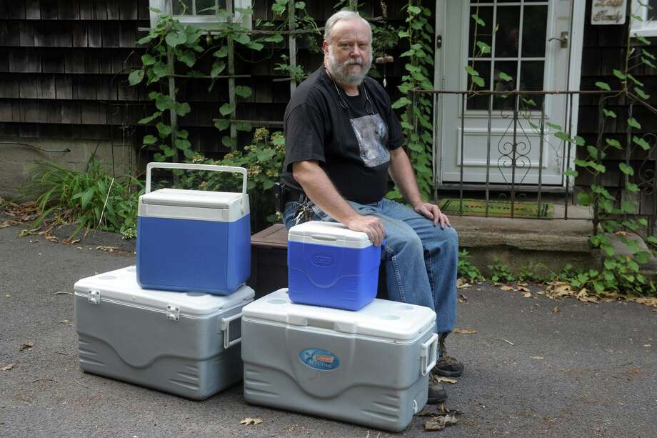 Jack Bradley sits with empty coolers outside his home in Fairfield on Aug. 14. Bradley struggled trying to keep perishables safe on ice after losing power during Tropical Storm Isaias. Photo: Ned Gerard / Hearst Connecticut Media / Connecticut Post