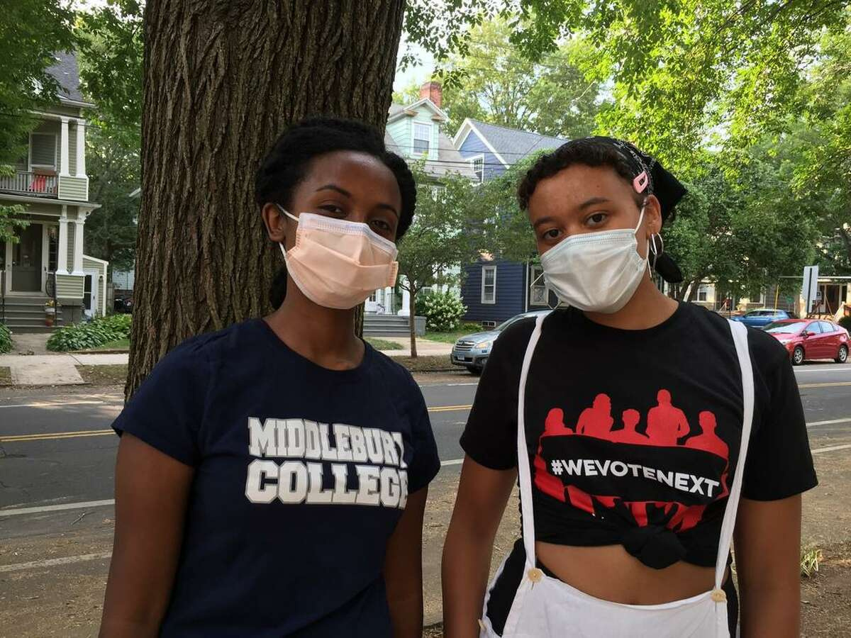 Wengel Kifle,left, and Remsen Welsh were among 30 young people who protested outside Mayor Justin's Elicker's house Friday demanding cuts to the police budget.