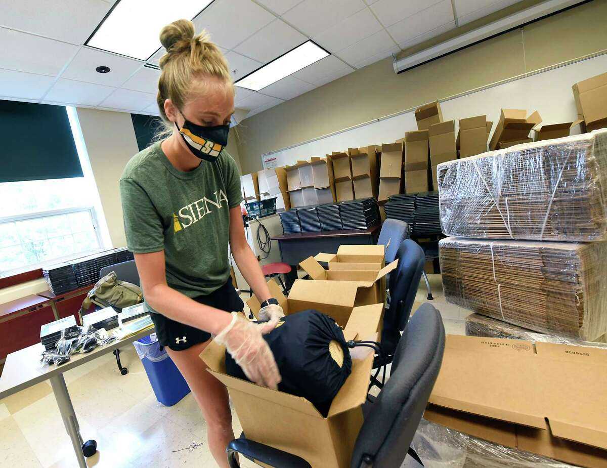 2013 Alumnus Elizabeth Ives, of Siena's Academic Affairs, helps pack gift boxes at the college to mail to the graduates on Friday, Aug. 14, 2020 in Colonie, N.Y. The gift boxes, which were mailed to take some of the sting out of the cancellation of commencement, include Siena logo blankets donated by Pretty Rugged, diploma covers, mortarboard tassels, a letter from Siena President Dr. Christopher Gibson, a photo frame and the graduation program. (Lori Van Buren/Times Union)