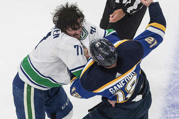 The Canucks' Zack MacEwen (left) and the Blues' Zach Sanford fight during the second period of a NHL Stanley Cup first-round playoff series Friday in Edmonton, Alberta.