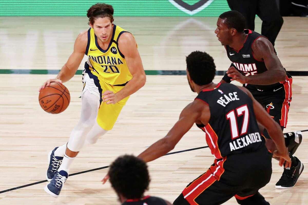 Indiana Pacers forward Doug McDermott (20) dribbles against Miami Heat guard Kendrick Nunn (top) and forward Kyle Alexander (17) during the second half of an NBA basketball game Friday, Aug. 14, 2020, in Lake Buena Vista, Fla. (Kim Klement/Pool Photo via AP)