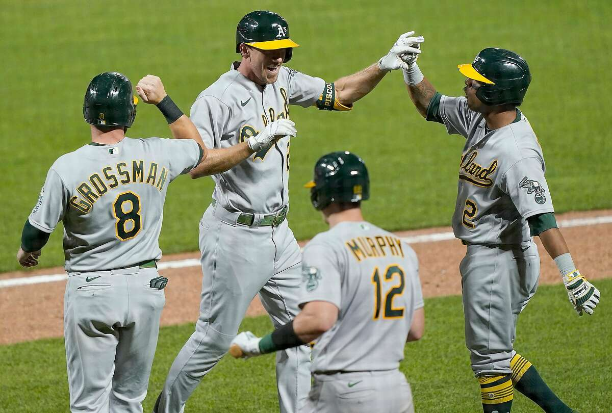 Stephen Piscotty #25, Khris Davis #2, Sean Murphy #12 and Robbie Grossman #8 of the Oakland Athletics celebrate after Piscotty hit a game-tying grand slam against the San Francisco Giants in the top of the ninth inning at Oracle Park on August 14, 2020 in San Francisco, Calif.