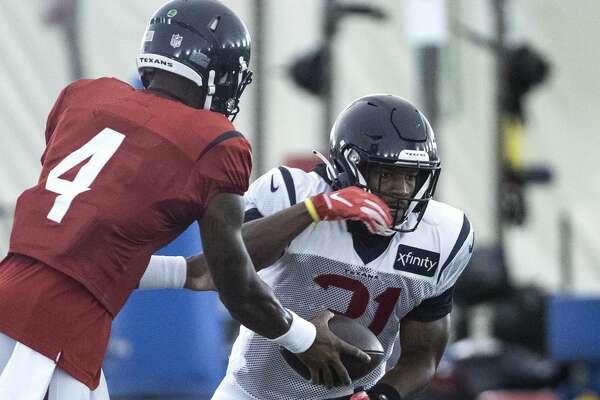 Houston Texans running back David Johnson (31) takes a handoff from quarterback Deshaun Watson (4) during an NFL training camp football practice Friday, Aug. 14, 2020, at The Houston Methodist Training Center in Houston.