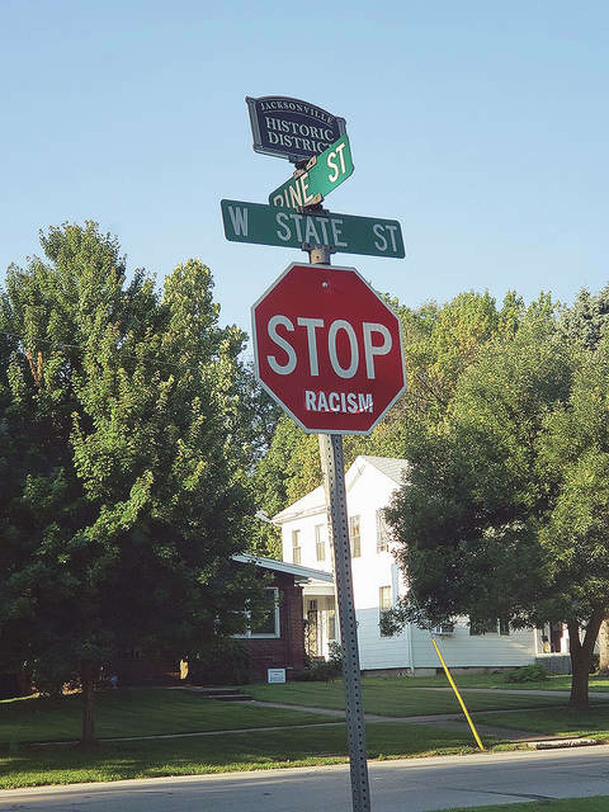 A bumper sticker added to a stop sign at West State and Pine streets creates an anti-racism message. Several of the stickers appeared Friday on stop signs in Jacksonville, but many had started peeling off by mid-morning.
