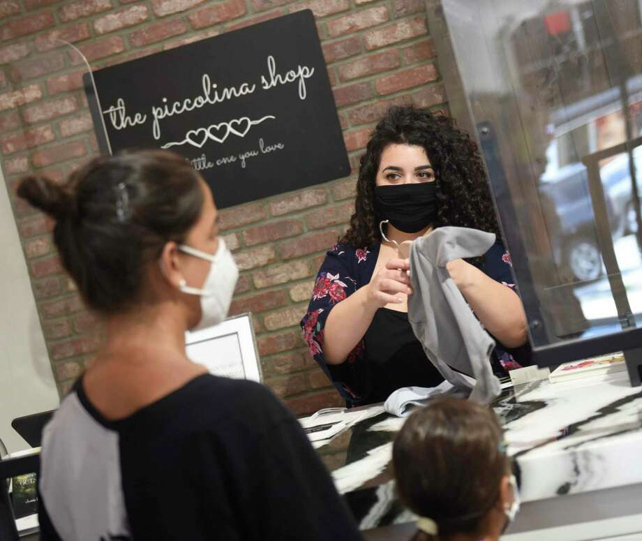 Co-owner Lena Scilipoti assists a customer at The Piccolina Shop in Greenwich, Conn. Thursday, Aug. 6, 2020. A trio of friends recently opened the store, which features a variety of baby and toddler clothing and toys. Photo: Tyler Sizemore / Hearst Connecticut Media / Greenwich Time