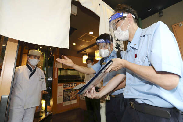 Fire department officials visit a restaurant in Nagoya, Japan, on Aug. 5, 2020, to advise on measures to prevent infections with the novel coronavirus.