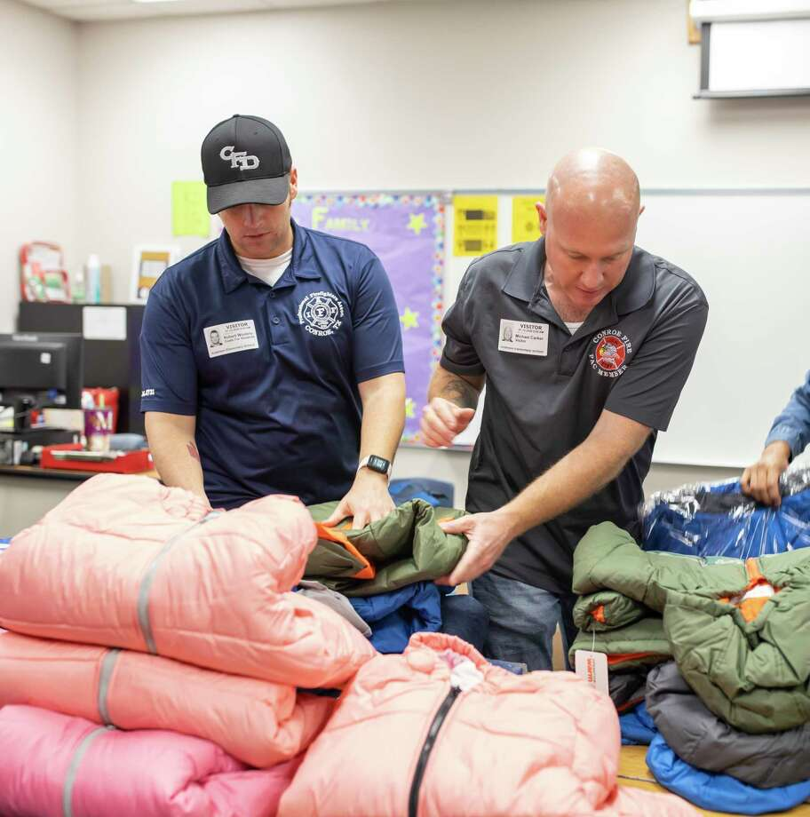 Robert Woolery and Michael Carker of the Conroe Professional Firefighters Foundation, prepare coats for, Operation Warm, at Anderson Elementary in Conroe, Wednesday, Jan. 15, 2020. The foundation has hosted the drive periodically over 7 years. Photo: Gustavo Huerta, Houston Chronicle / Staff Photographer / Houston Chronicle
