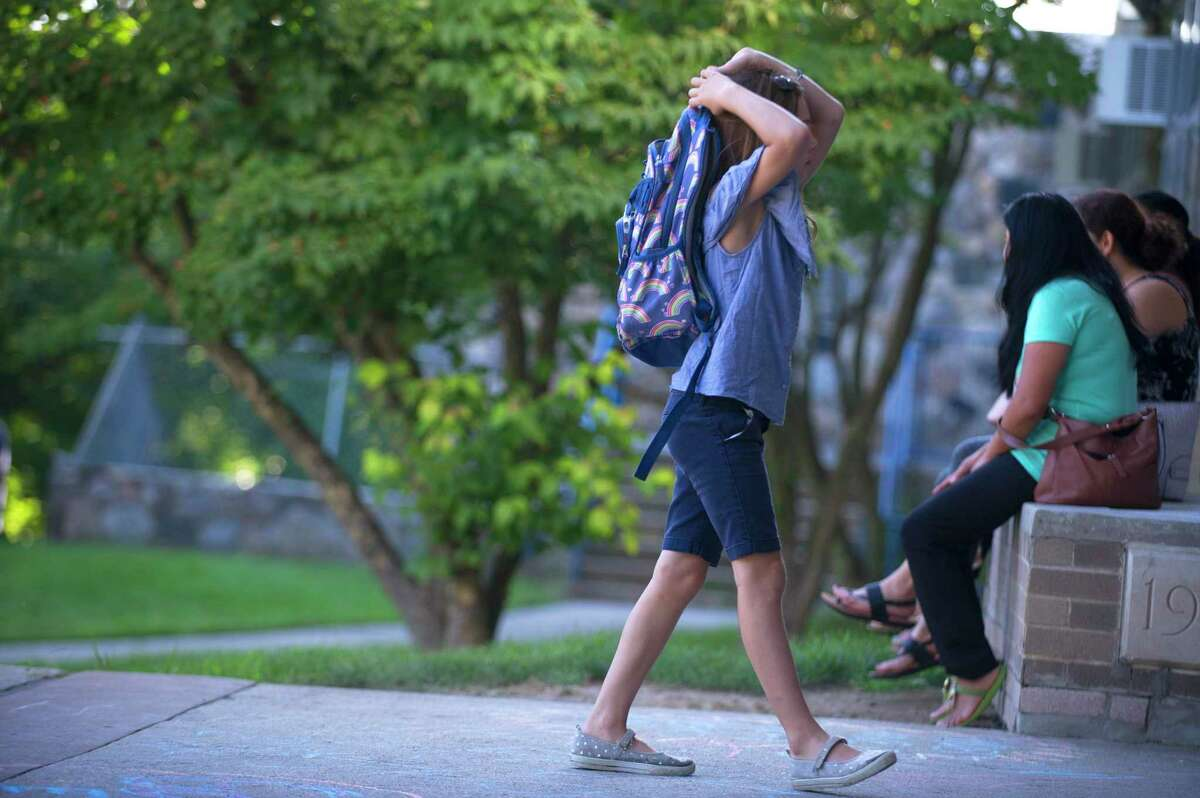 A girl begrudgingly walks into Northeast Elementary School during the first day of school in Stamford, Conn. on Thursday, Aug. 30, 2018. Will students in the hybrid model be able to follow along through live streaming on home days? This is still being worked out, said Amy Beldotti, associate superintendent for teaching and learning, but a portion of the district's plan allows for this type of technology.