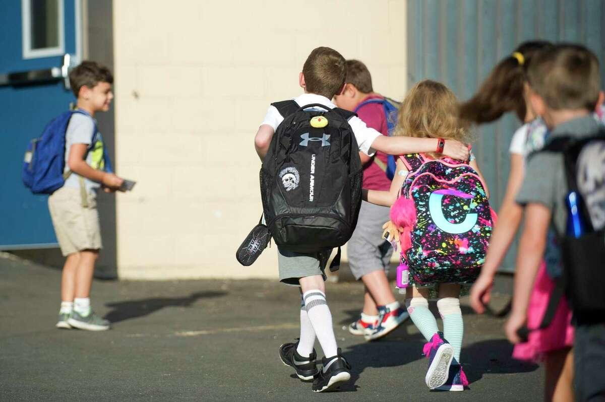 A boy puts his arm around his younger sister as they walk into Northeast Elementary School on the first day of school in Stamford, Conn. on Thursday, Aug. 30, 2018. Is there enough bandwidth for every school to be streaming every class? City IT workers have told Superintendent Tamu Lucero there is enough, but capabilities have not been tested yet.