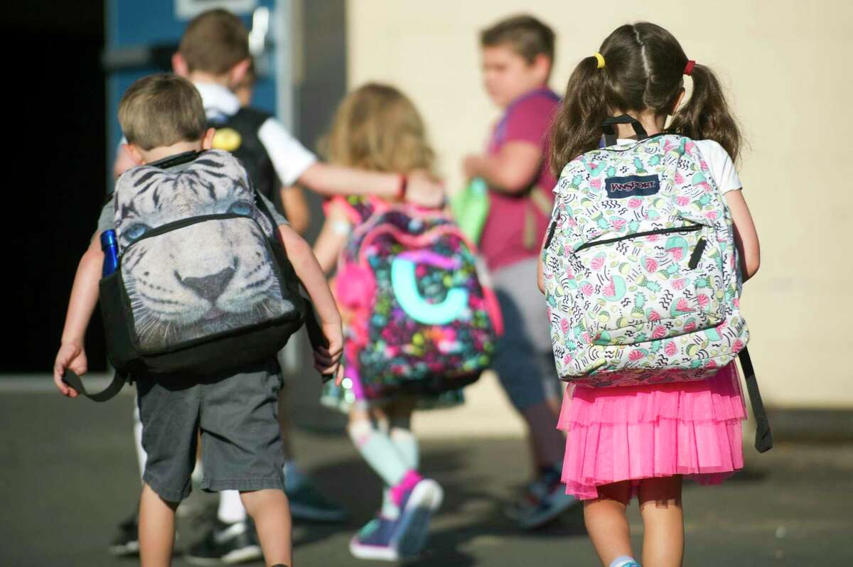 Students walk into Northeast School with their backpacks on during the first day of school in Stamford, Conn. on Thursday, Aug. 30, 2018. Why was the alternating-day hybrid schedule chosen, as opposed to a static schedule each week? Beldotti said the simple answer is that the alternating days model would create less of a gap between times students are in school buildings.