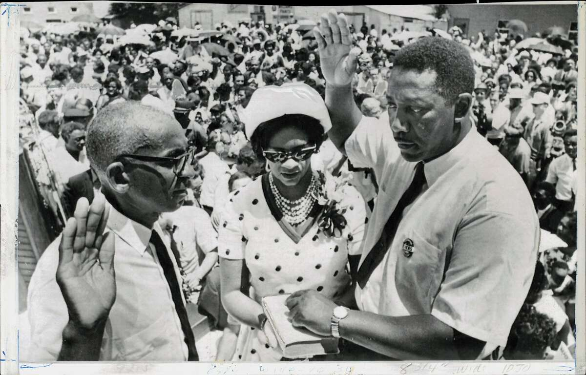 Evers, Charles (Mayor) (Fayette, Mississippi). Charles Evers (right) takes oath as the new mayor of Fayette, Mississippi. Justice of Peace Willie Thompson administers oath as Mrs. Evers holds Bible.