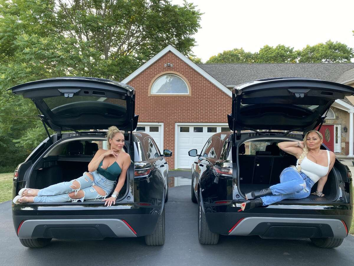 Darcey and Stacey sitting in trunk of cars in front of home driveway