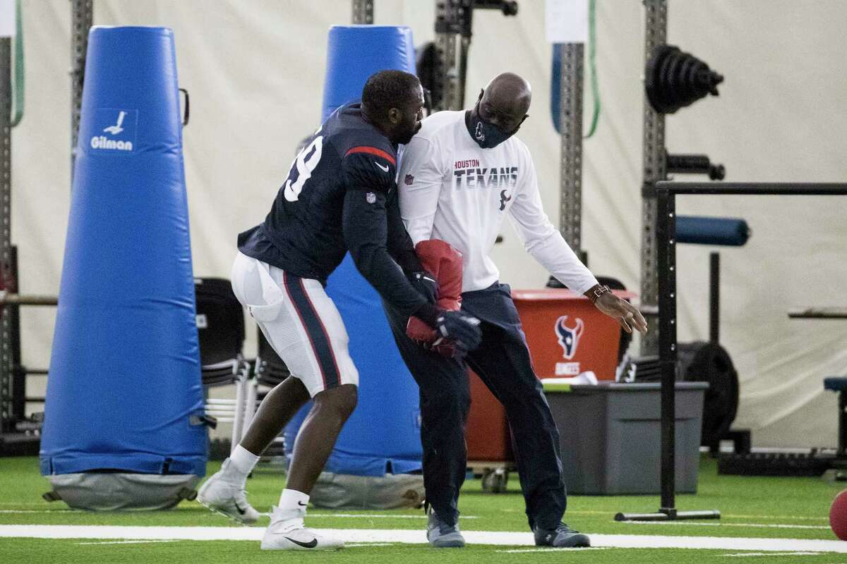 Houston Texans linebacker Whitney Mercilus (59) works with outside linebackers coach Chris Rumph during an NFL training camp football practice Saturday, Aug. 15, 2020, at The Houston Methodist Training Center in Houston.