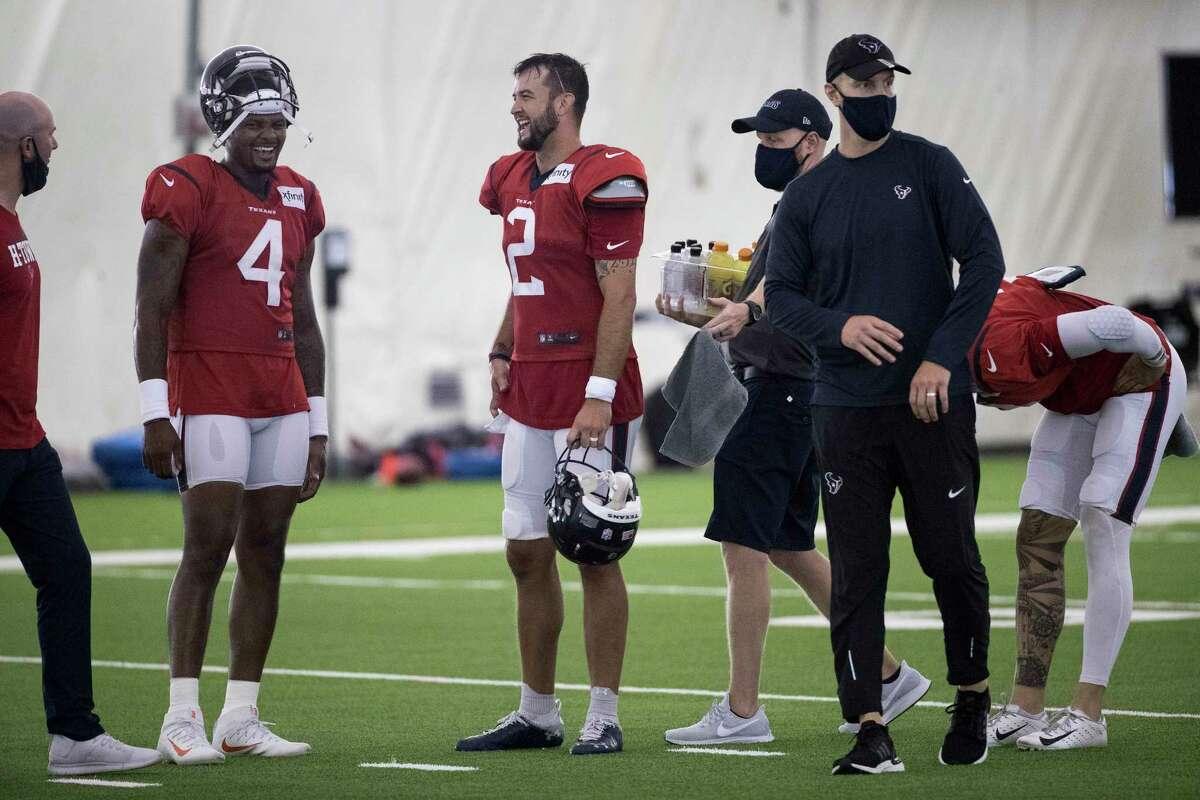 Houston Texans quarterbacks Deshaun Watson (4) and AJ McCarron (2) take a break between drills during an NFL training camp football practice Saturday, Aug. 15, 2020, at The Houston Methodist Training Center in Houston.
