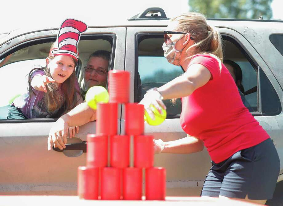 Emma Rose Moore throws a ball at stacked cans as part of Operation Backpack Drive-Thru at the East Texas Dream Center, Saturday, Aug. 15, 2020, in Splendora. The event provided more than 350 families in need with a backpack full of school supplies. Photo: Jason Fochtman, Houston Chronicle / Staff Photographer / 2020 © Houston Chronicle