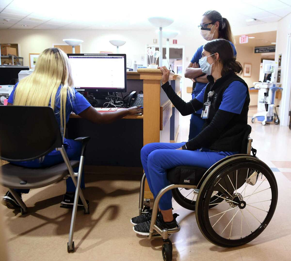 Registered nurse Lindsey Runkel, right, speaks with charge nurse Shaniya Tripp, left, at Yale New Haven Hospital's kidney and liver transplant unit on Aug. 11, 2020. In the background is registered nurse Amy Smith.