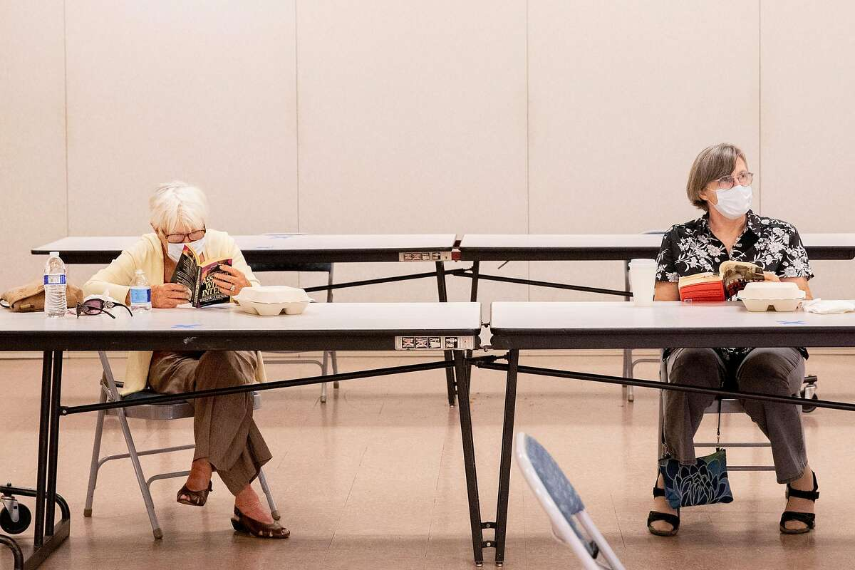(From left) Martinez residents Patricia Adina and Claudine Thomas sit socially distanced from one another as they read at a cooling center set up inside Martinez Senior Community Center in Martinez, Calif. Saturday, August 15, 2020. Mulitple cities activated cooling centers at civic buildings and senior centers Saturday as triple digit temperatures are forecast for most locations across the Bay Area particularly in the East Bay and farther south. The COVID-19 pandemic has added extra precautions for check-in and assistance at cooling centers. Heat advisories are in effect throughout the Bay Area through the weekend.