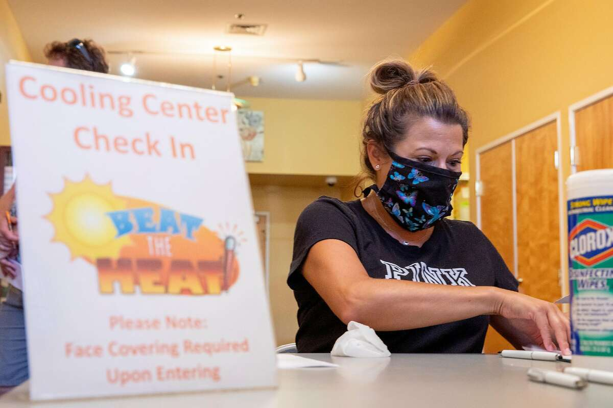 Martinez Senior Community Center supervisor Gina Gravert wears a mask while disinfecting pens after checking residents into the cooling center inside Martinez Senior Community Center in Martinez, Calif. Saturday, August 15, 2020. Multiple cities activated cooling centers at civic buildings and senior centers Saturday as triple digit temperatures are forecast for most locations across the Bay Area particularly in the East Bay and farther south. The COVID-19 pandemic has added extra precautions for check-in and assistance at cooling centers. Heat advisories are in effect throughout the Bay Area through the weekend.