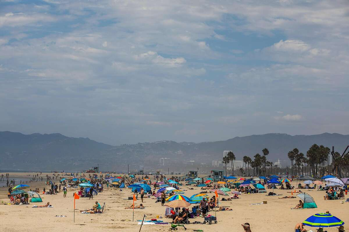 People enjoy the beach amid the severe heat wave in Venice, California on August 15, 2020. - The worst heat wave in several years caused rolling blackouts August 14, 2020 due to power shortages and is setting up dangerous conditions across California. (Photo by Apu GOMES / AFP) (Photo by APU GOMES/AFP via Getty Images)
